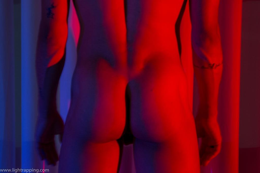 homem nu, de pé, visto entre o meio das costas e o meio das coxas, iluminado com luz vermelha e azul. Ao fundo, uma cortina com as dobras iluminadas em vermelho e azul.